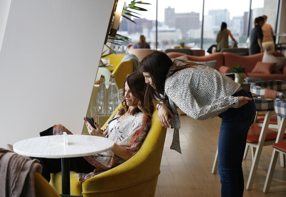BOSTON, MA - JULY 23: Karen Cahn, Founder & CEO of iFundWomen, left, works on her phone as Kate Anderson, Co-Founder and Operations Director at iFundWomen, leans in to chat, at The Wing in Boston on July 23, 2019. The Wing is supposed to be more than a co-working space. When the first location opened in New York in 2016, the intention was to be a womens club of this era. The mission: the professional, civic, social, and economic advancement of women through community. (Photo by Jessica Rinaldi/The Boston Globe via Getty Images)