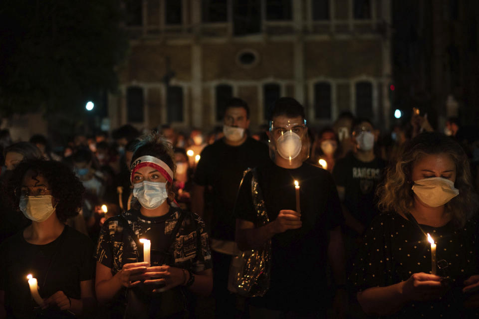 Demonstrators march holding candles honoring the victims of the deadly explosion at Beirut port which devastated large parts of the capital, in Beirut, Lebanon, Sunday, Aug. 9, 2020. (AP Photo/Felipe Dana)