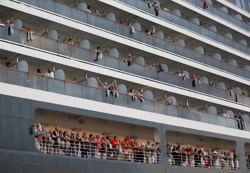 Passengers wave their hands onboard MS Westerdam, a cruise ship that spent two weeks at sea after being turned away by five countries over fears that someone aboard might have the coronavirus, as it docks in Sihanoukville