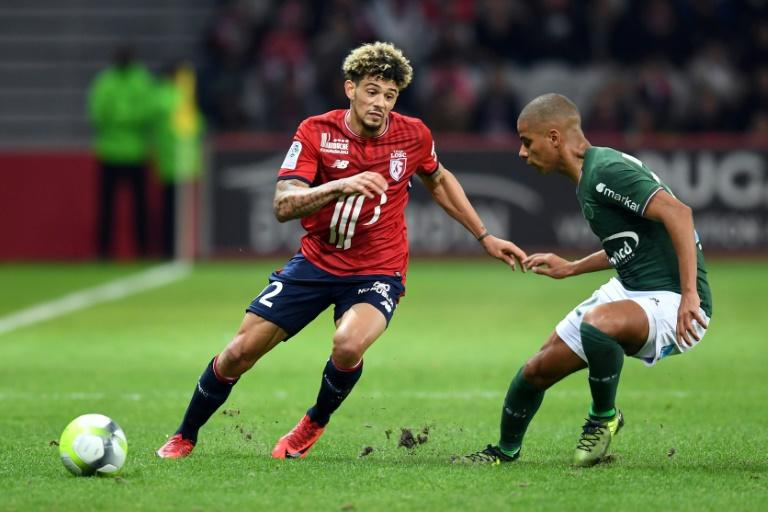 Lille's Kevin Malcuit (L) vies with Saint-Etienne's Kevin Monnet-Paquet during a match at the Pierre-Mauroy Stadium near Lille on November 17 2017
