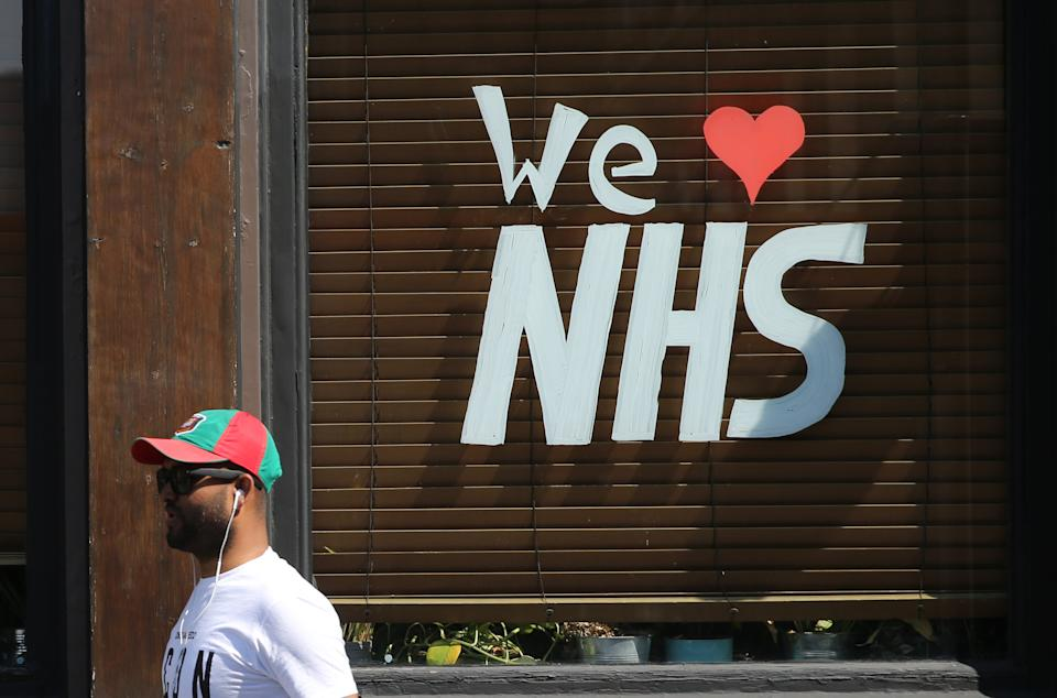 "A man walks past a message reading ""We love NHS"" in the window of a closed-down pub outside The Royal London Hospital in Whitechapel, east London, as the UK continues in lockdown to help curb the spread of the coronavirus. Picture date: Friday April 24, 2020."