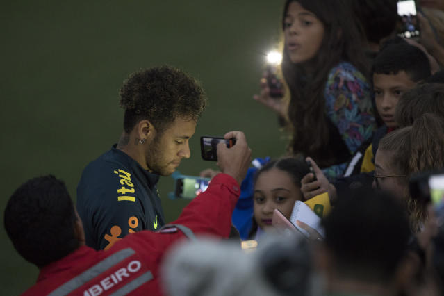 Brazil's Neymar gives autographs to fans after a practice session of the Brazilian national soccer team ahead the World Cup in Russia, at the Granja Comary training center In Teresopolis, Brazil, Friday, May 25, 2018. (AP Photo/Leo Correa)