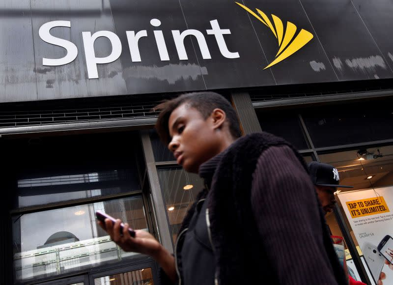 FILE PHOTO: A woman uses her phone as she walks past a Sprint store in New York's financial district
