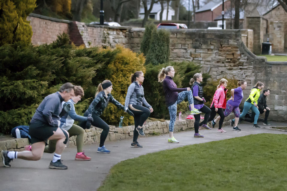 """People take part in """"Boot Camp"""" exercise class in Springhead Park, following the easing of England's lockdown to allow far greater freedom outdoors, in Rothwell, England, Monday March 29, 2021. England is embarking on a major easing of its latest coronavirus lockdown that came into force at the start of the year, with families and friends able to meet up in outdoor spaces and many sports permitted once again. Under Monday's easing, groups of up to six, or two households, can socialize in parks and gardens once more, while outdoor sports facilities can reopen after the stark stay-at-home order, which has seen new coronavirus cases fall dramatically over the past three months, ended. (Danny Lawson/PA via AP)"""