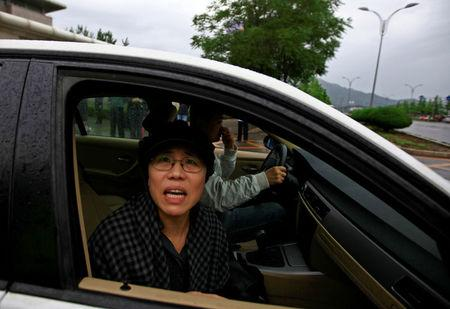 FILE PHOTO: Liu Xia, wife of jailed Nobel Peace Prize Laureate Liu Xiaobo, looks out of a car window after a trial outside a court in the Huairou district of Beijing, China June 9, 2013. REUTERS/Petar Kujundzic/File Photo