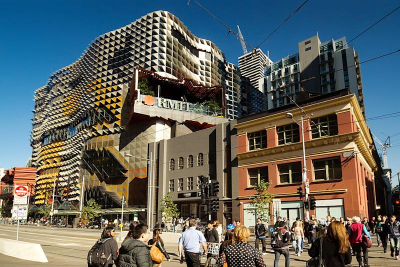People cross the street in front of an RMIT campus building.