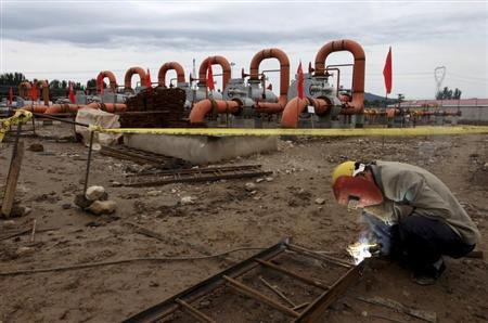 A labourer welds a steel frame next to natural gas pipes at a receiving terminal on the outskirts of Beijing, September 23, 2013. REUTERS/Stringer