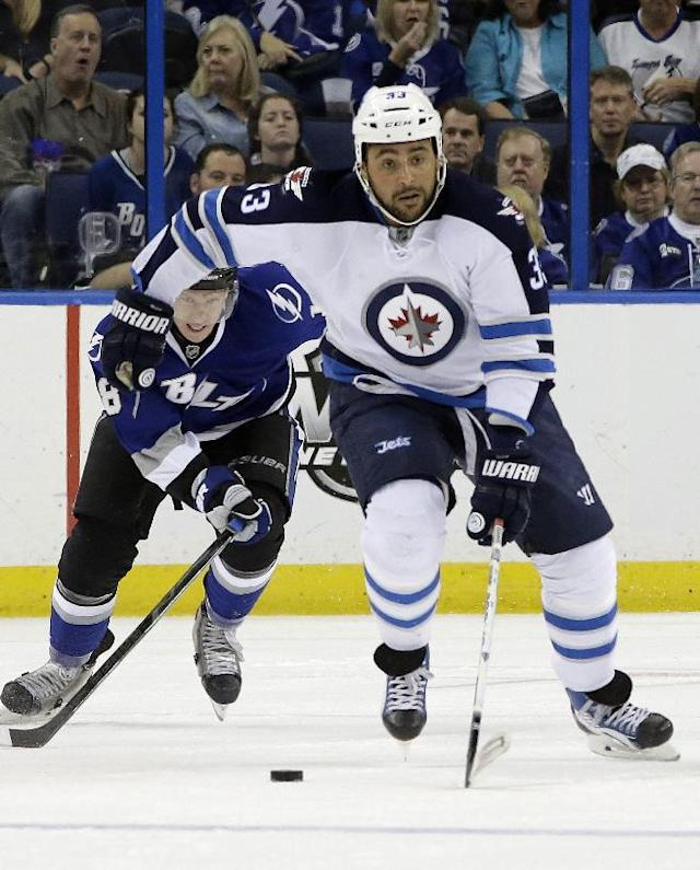 Winnipeg Jets defenseman Dustin Byfuglien (33) breaks out after getting past Tampa Bay Lightning left wing Ondrej Palat (18), of the Czech Republic, during the first period of an NHL hockey game on Saturday, Dec. 7, 2013, in Tampa, Fla. (AP Photo/Chris O'Meara)