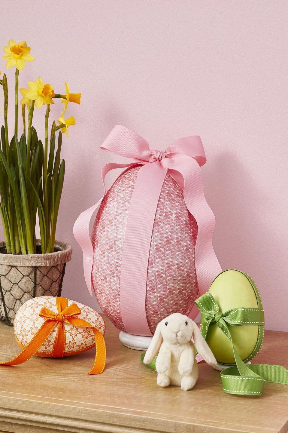 """<p>Craft this giant egg and then fill it with surprises like candy and toys to <em>really</em> impress the kids this year.</p><p><strong><em><a href=""""https://www.womansday.com/home/crafts-projects/g2216/easter-eggs/?slide=2"""" rel=""""nofollow noopener"""" target=""""_blank"""" data-ylk=""""slk:Get the Surprise Egg tutorial."""" class=""""link rapid-noclick-resp"""">Get the Surprise Egg tutorial.</a></em></strong></p><p><strong><a class=""""link rapid-noclick-resp"""" href=""""https://www.amazon.com/VILAVITA-Cupcake-Dessert-Birthday-Celebration/dp/B074TF6YB4?tag=syn-yahoo-20&ascsubtag=%5Bartid%7C10070.g.1751%5Bsrc%7Cyahoo-us"""" rel=""""nofollow noopener"""" target=""""_blank"""" data-ylk=""""slk:SHOP CAKE STANDS"""">SHOP CAKE STANDS</a></strong></p>"""