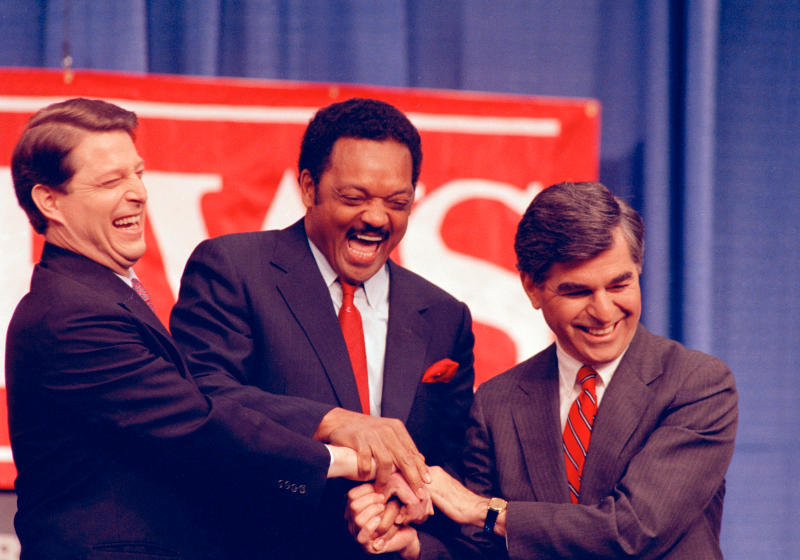 Democratic presidential hopefuls Al Gore, Jese Jackson and Michael Dukakis join hands before a debate in New York City on April 13, 1988.
