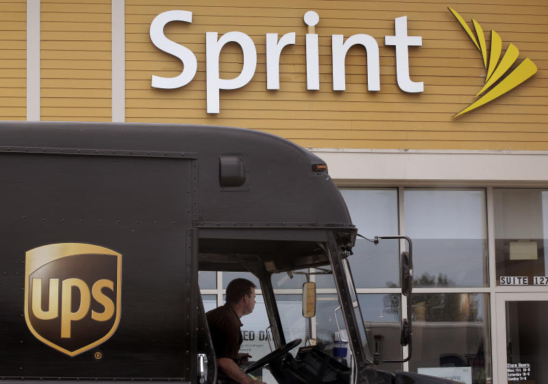 FILE - In this Thursday, July 19, 2012 file photo, a UPS truck stops in front of a Sprint store at the Derby Street Shoppes in Hingham, Mass.  Sprint Netxel Corp. is reporting their fourth quarter 2012 earnings on Thursday, Feb. 7, 2013. (AP Photo/Stephan Savoia)