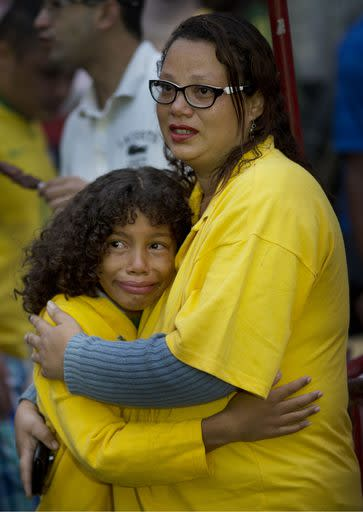 Brazil soccer fans embrace as they watch their team lose to Germany via a live telecast of the World Cup semifinal game in Sao Paulo, Brazil, Tuesday, July 8, 2014. (AP Photo/Rodrigo Abd)