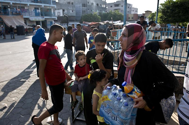 A Palestinian woman displaced from her home when fighting broke out between Israel and Hamas militants over four weeks ago, carries water bottles given to her as food handouts on August 16, 2014 at a United Nations school in Jabalia