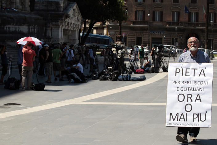 """Vittorio Colavitto walks with a poster reading """"Mercy for Berlusconi and Italians now or never"""" outside Italy's highest court where Berlusconi's case on tax fraud will be decided, in Rome, Wednesday, July 31, 2013. Berlusconi's political fate is in the hands of Italy's highest court, which is hearing arguments in the former premier's fraud conviction. Berlusconi has been convicted of tax fraud in a complex TV rights transaction for his Mediaset network, and sentenced to four-years in prison with a five-year ban on public office. This is his final appeal. A decision could come later Wednesday or Thursday. (AP Photo/Gregorio Borgia)"""