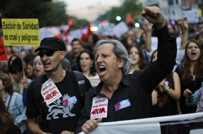"""Protestors hold a banner reading """"to exclude people from the health care system is dangerous and cruel"""" as they shout slogans against healthcare austerity measures announced by the Spanish government and to defend the public healthcare system in Madrid, Spain, Saturday, Oct. 6, 2012. Hundreds of Spaniards concerned with government cuts to healthcare and civil servants hit with another freeze on their wages for next year hold a protest in downtown Madrid. (AP Photo/Andres Kudacki)"""