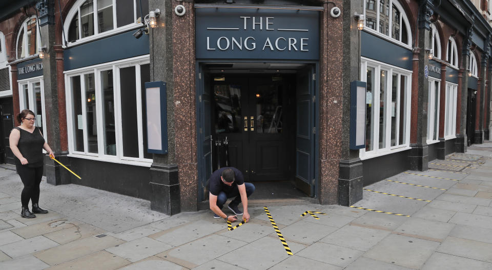 Employees mark the outside of a pub with tape for social distancing, prior to reopening, in London, Tuesday, June 30, 2020. Tuesday marked 100 days since Britain's Prime Minister Boris Johnson detailed a short list of reasons why individuals could leave their homes as he ordered the immediate closure of all shops selling non-essentials. (AP Photo/Frank Augstein)