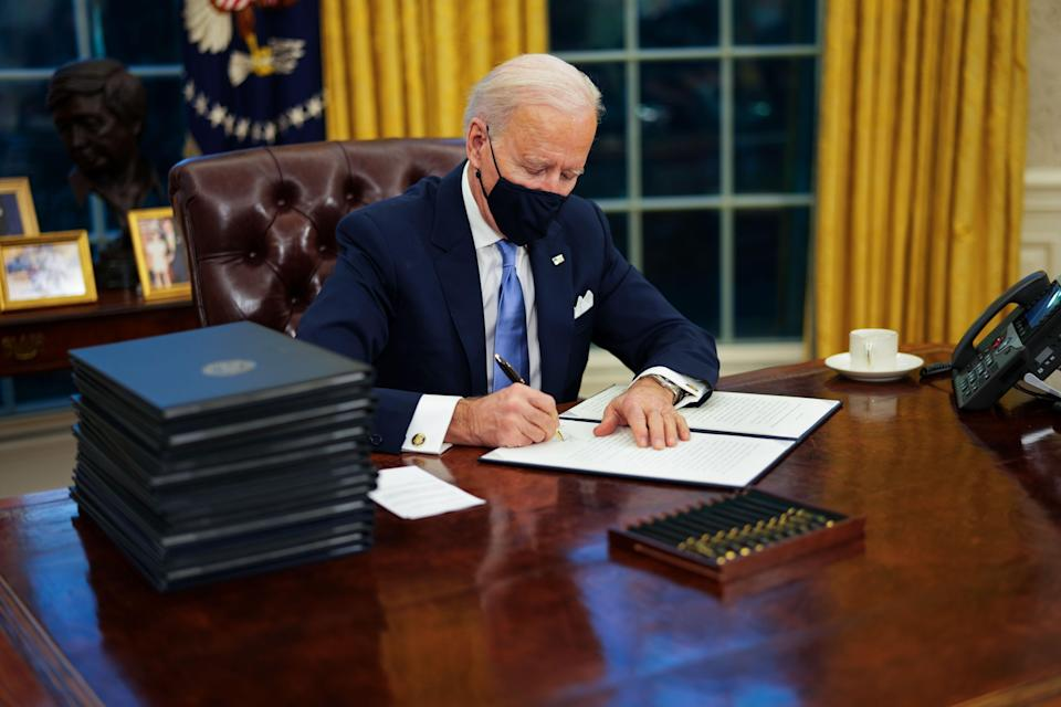 US President Joe Biden signs executive order on Covid-19 during his first minutes in the Oval Office (EPA-EFE)