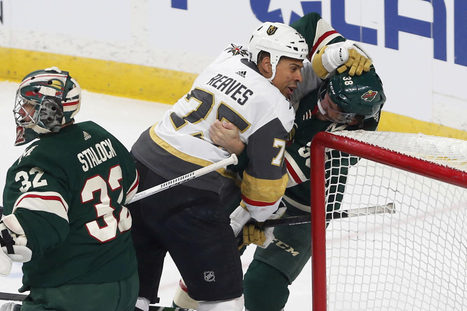 Vegas Golden Knights' Ryan Reaves, center, shoves Minnesota Wild's Ryan Hartman in the first period of an NHL hockey game Tuesday, Feb. 11, 2020, in St. Paul, Minn. (AP Photo/Jim Mone)