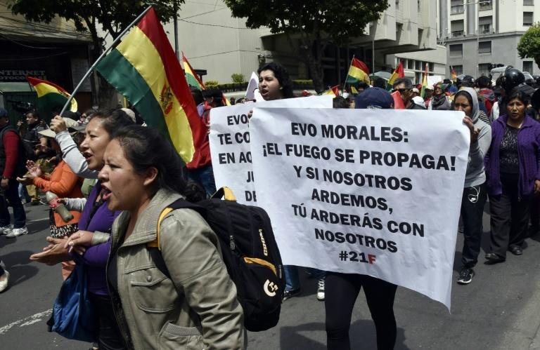 "People with a sign reading ""Evo Morales: Fire spreads! And if we burn, you will burn with us,"" march against the nomination of the Bolivian president as candidate for reelection for the October 2019 elections, in La Paz on December 6, 2018"