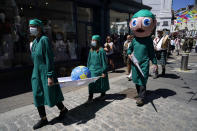Activists dressed as medical personnel hold a giant syringe and a globe on a stretcher as they march through the streets during a demonstration around the meeting of the G7 in Falmouth, Cornwall, England, Saturday, June 12, 2021. Leaders of the G7 gather for a second day of meetings on Saturday, in which they will discuss COVID-19, climate, foreign policy and the economy. (AP Photo/Alberto Pezzali)