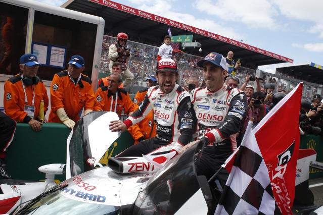 Drivers of the Toyota TS050 Hybrid No8 of the Toyota Gazoo Racing Team Sebastien Buemi of Switzerland, right on the car and Fernando Alonso of Spain celebrate after winning the 86th 24-hour Le Mans endurance race, in Le Mans, western France, Sunday, June 17, 2018. (AP Photo/Thibault Camus)