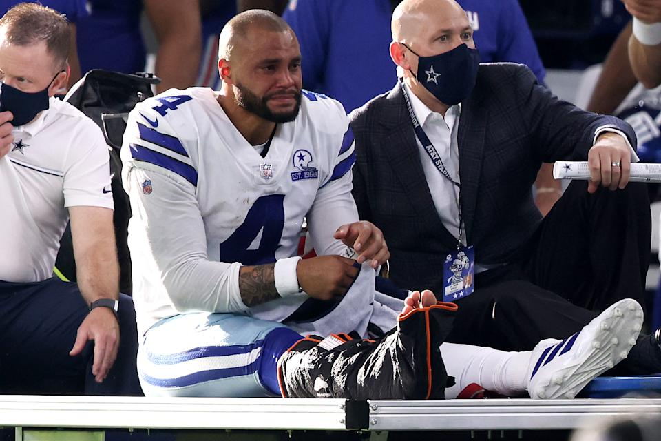 Dak Prescott of the Dallas Cowboys is carted off the field after sustaining a leg injury