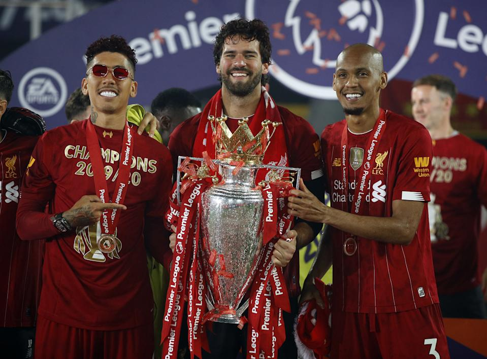 Liverpool's Brazilian players (from left) Roberto Firmino, Alisson Becker and Fabinho celebrate with the Premier League trophy. (PHOTO: Phil Noble/PA Images via Getty Images)