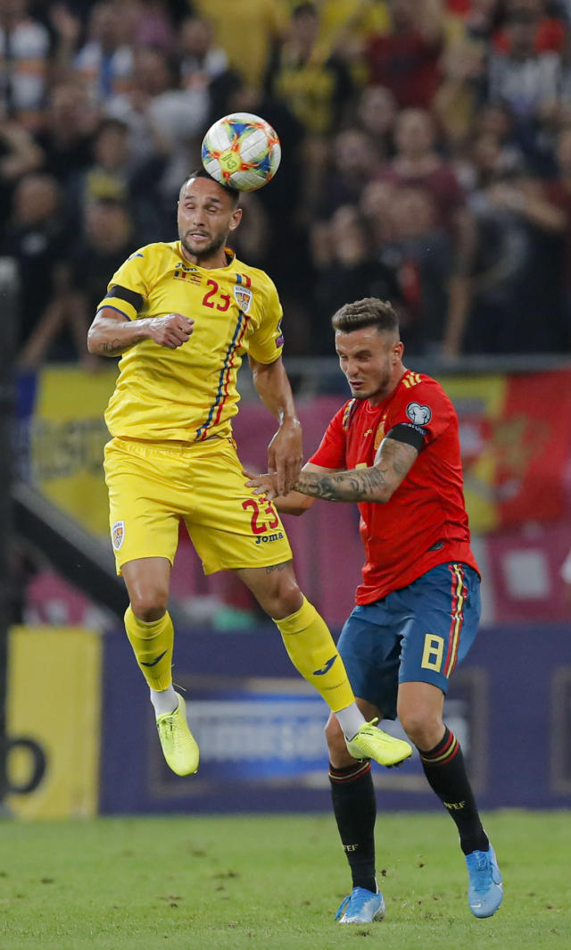 Romania's Florin Andone, left jumps for a header with Spain's Sergi Roberto during the Euro 2020 group F qualifying soccer match between Romania and Spain, at the National Arena stadium in Bucharest, Romania, Thursday, Sept. 5, 2019. (AP Photo/Vadim Ghirda)