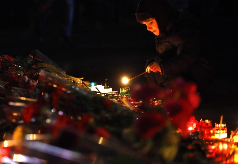 A child lights candles at a memorial for those killed in recent violence in Kiev's Independence Square