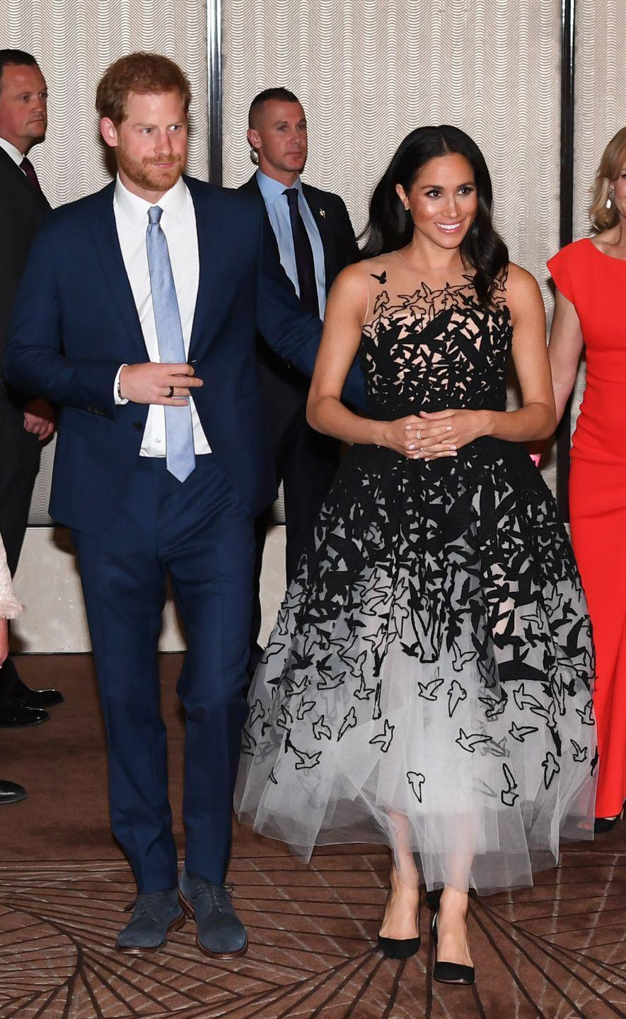 <p>The Duchess of Sussex wowed well-wishers when she stepped out for the Australian Geographic Society Awards in Sydney, Australia in an elaborate Oscar de la Renta gown. The black and white dress featured an illusion neckline, an abstract print, and a full tulle skirt. </p>