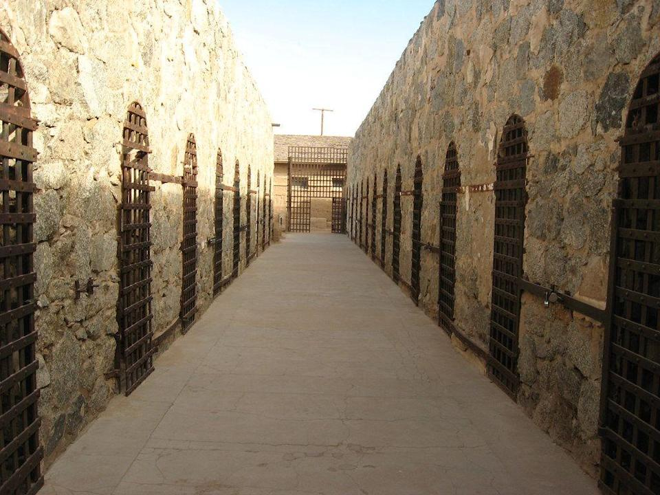 """<p><strong>Yuma Territorial Prison - Yuma, AZ</strong></p><p>The Yuma-set prison opened its doors in 1876 and operated for 33 years. During the height of its operation, the prison housed murderers and thieves, but that's not all. <a href=""""https://www.azcentral.com/story/news/local/arizona-contributor/2016/10/11/who-haunts-old-yuma-territorial-prison/91870898/"""" rel=""""nofollow noopener"""" target=""""_blank"""" data-ylk=""""slk:Over 100 people died on the site,"""" class=""""link rapid-noclick-resp"""">Over 100 people died on the site,</a> and the worst inmates were chained to ring-bolts in what was known as the """"dark cell."""" Visitors can still explore the aforementioned space... if they're brave enough. Many have even reported being """"touched"""" by unseen forces.</p><p>Photo: Flickr/<a href=""""https://www.flickr.com/photos/kenlund/4406912674/in/photolist-a2iRfq-7HqApU-7HqyxE-7HmgPZ-7HqBBd-7HqzB1-7HqC8G-7HmDwF-89SBMQ-br2gwc-7HqcjN-7HqxWN-7HqyZQ-7Hqxqj-7HmFu4-7HmNCx-7HqmDY-7HmF8e-7HmEQD-7HmBTV-7HmBrc-7HmE6c-7Hms3v-7HqwXw-7Hmsg8-7HqwxU-7HmEoc-7Hqnoh-7Hqygh-7HqKfG-7HmqCX-7HmrRP-7Hqowm-7HmsJe-7Hq2xo-7HqJZE-7Hy3CS-89SBTW-89SCbS-G6ntDr-8bFbpi-8bFbwX-8bFbSK-sb296B-rxkJuu"""" rel=""""nofollow noopener"""" target=""""_blank"""" data-ylk=""""slk:Ken Lund"""" class=""""link rapid-noclick-resp"""">Ken Lund</a></p>"""