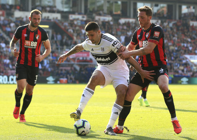 Fulham's Aleksandar Mitrovic, center, and Bournemouth's Dan Gosling battle for the ball during the English Premier League soccer match between Bournemouth and Fulham at the Vitality Stadium, Bournemouth England. Saturday, April 20, 2019. (Mark Kerton/PA via AP)