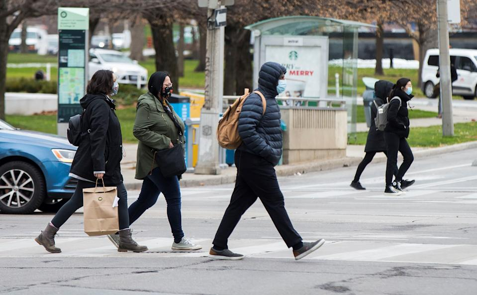 TORONTO, Nov. 24, 2020 -- People wearing face masks cross a street in Toronto, Canada, on Nov. 24, 2020. The number of COVID-19 cases in Canada continued to increase as the country reported a total of 340,388 cases and 11,592 deaths as of Tuesday afternoon, according to CTV. (Photo by Zou Zheng/Xinhua via Getty) (Xinhua/Zou Zheng via Getty Images)