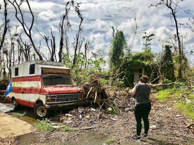 <p>Megan Vazquez photographs the destruction around an abandoned van and hot dog stand near her hometown of Bayamon, Puerto Rico three weeks after Hurricane Maria devastated the island. (Photo: Caitlin Dickson/Yahoo News) </p>