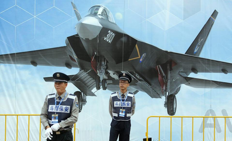 Security guards in front of poster of FC-31 J-31 J-35 fighter jet