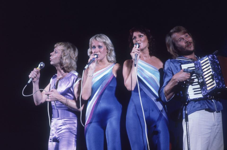 1979:  Swedish musical group ABBA performing on stage, (L-R:) Bjorn Ulvaeus, Agnetha Faltskog, and Anni-Frid Lyngstad sing while Benny Andersson plays the accordion.  All wear blue and lavender spandex outfits.  (Photo by Bob Grant/Fotos International/Getty Images)