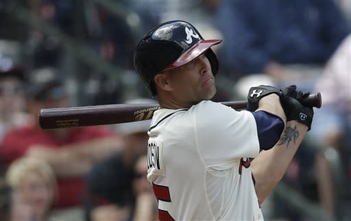 Atlanta Braves' Tim Hudson (15) follows through with an RBI-base hit in the sixth inning of a baseball game against the Chicago Cubs in Atlanta, Sunday, April 7, 2013. (AP Photo/John Bazemore)