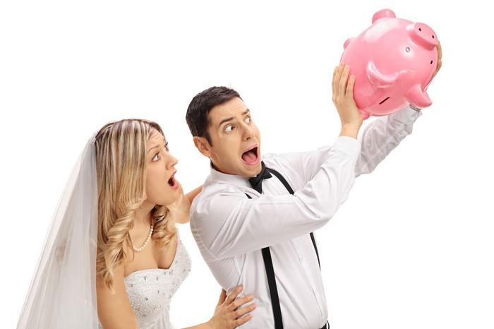 We see a bride and groom, holding an empty piggy bank upside down while looking alarmed, with their mouths open.