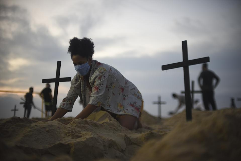 RIO DE JANEIRO, BRAZIL â JUNE 11 : A protester digs a mock grave on Copacabana beach symbolizing deaths due to the coronavirus (COVID-19) and protest against governments actions towards the pandemic, in Rio de Janeiro, Brazil on June 11, 2020. Act calls for transparency and attitude change from the government to fight the virus. The novel coronavirus continued to spread throughout Latin America on Thursday, with the death toll climbing to over 72,000. The region is currently considered the epicenter of the health crisis and accounts for nearly half of the deaths and cases worldwide. Residents of Rio de Janeiro woke up Thursday to see 100 open graves at the city's most emblematic beach. During the night, Brazilians critical of President Jair Bolsonaroâs response to the coronavirus pandemic dug 100 graves and stuck black crosses in the sand of Copacabana beach in a tribute to the nearly 40,000 people who have died so far in Brazil from COVID-19. (Photo by Fabio Alarico Teixeira/Anadolu Agency via Getty Images)