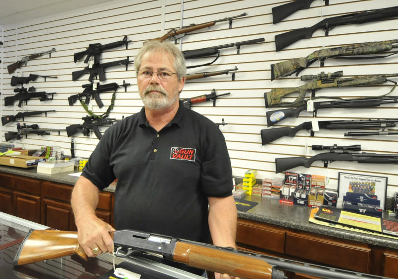 Randy Hodges holds a firearm at the Gun Vault in High Point N.C. Monday July 23, 2012. Issues of gun sales, especially assault rifles and large amounts of ammunition, have come into the forefront since a single gunman entered an Aurora, Colo., theater shortly after midnight Friday and began firing indiscriminately at men, women and children. (AP Photo/The Enterprise,Sonny Hedgecock)