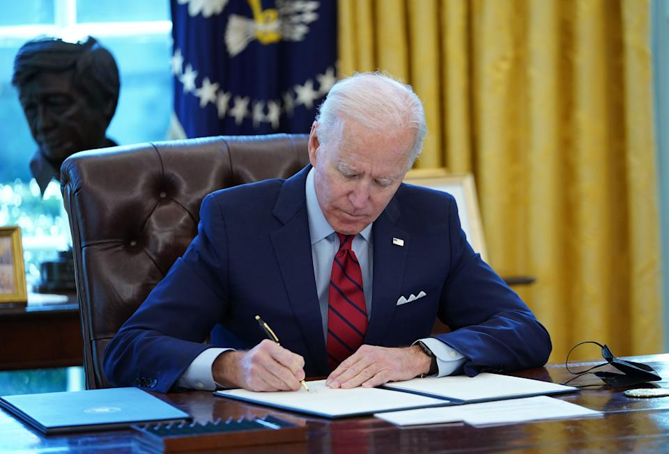 US President Joe Biden signs executive orders on health care, in the Oval Office of the White House in Washington, DC, on January 28, 2021. - The orders include reopening enrollment in the federal Affordable Care Act. (Photo by MANDEL NGAN / AFP) (Photo by MANDEL NGAN/AFP via Getty Images)