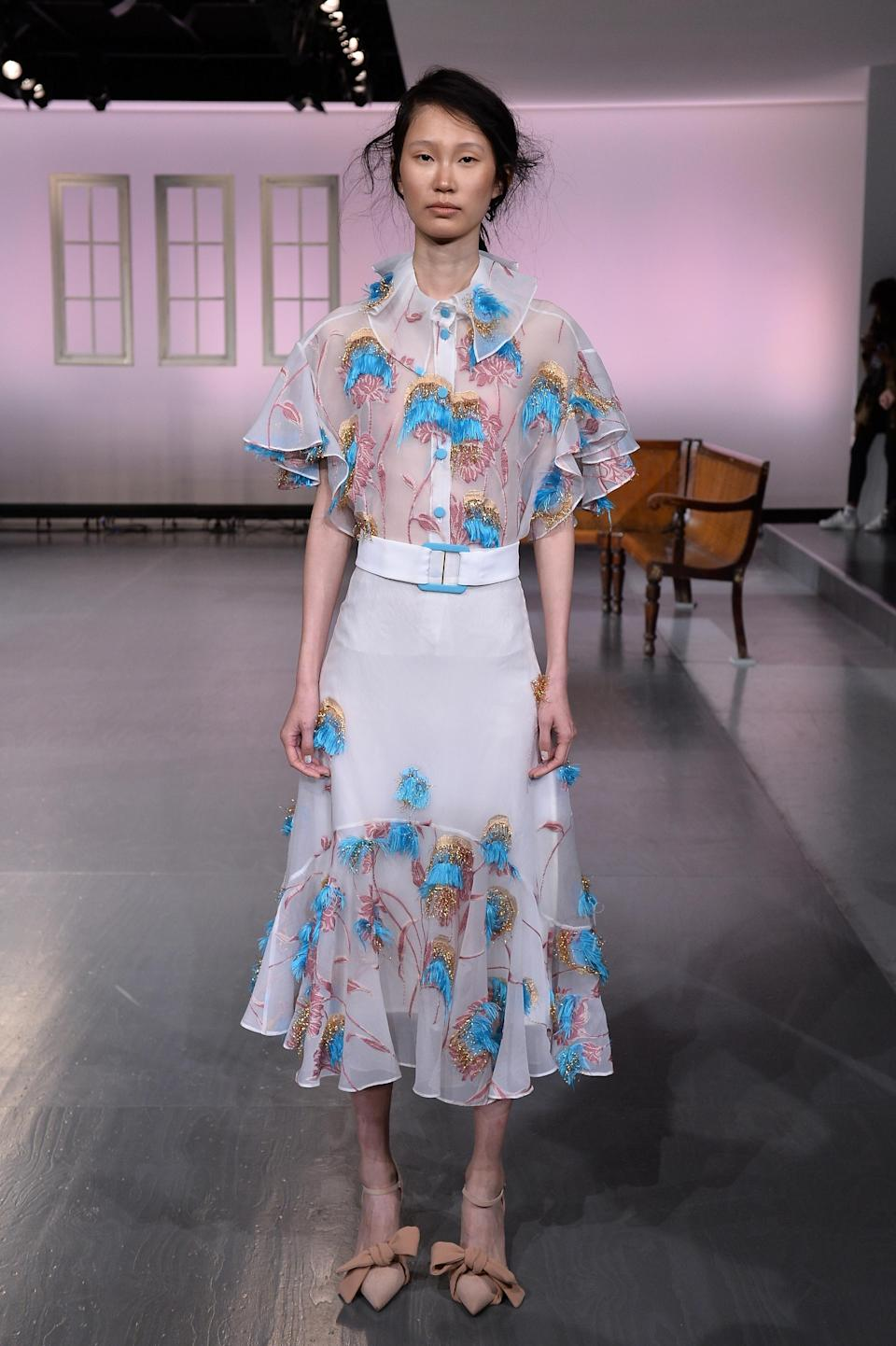 <p>A sheer blouse and bright detailing breaks up an all-white look. </p>