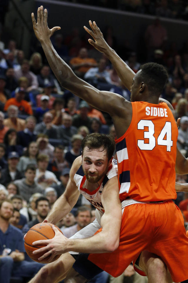 Virginia forward Jay Huff, left, tries to get around Syracuse forward Bourama Sidibe (34) during the second half of an NCAA college basketball game in Charlottesville, Va., Saturday, Jan. 11, 2020. Syracuse defeated Virginia 63-55 in overtime. (AP Photo/Steve Helber)