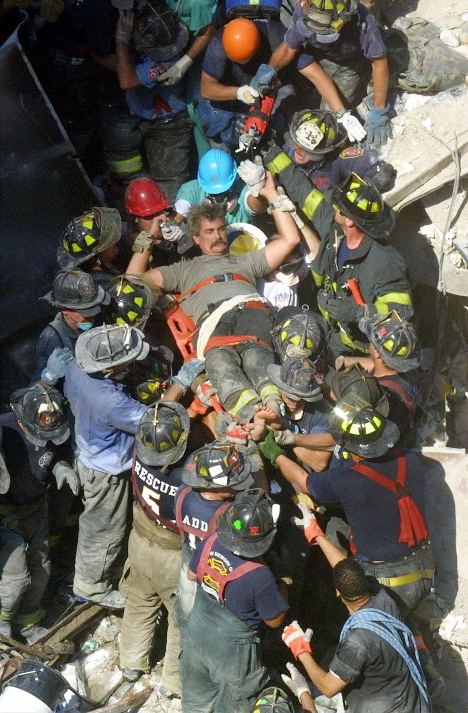 A rescue worker is pulled from the rubble (Getty)