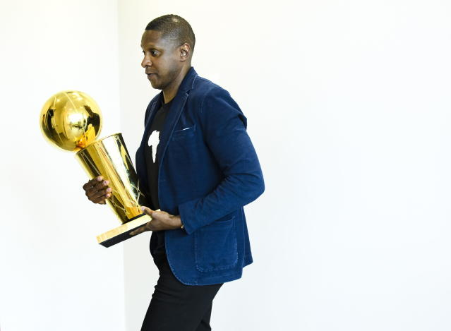 Toronto Raptors NBA basketball team president Masai Ujiri carries the Larry O'Brien Trophy as he leaves an end-of-season press conference in Toronto, Tuesday, June 25, 2019. (Nathan Denette/The Canadian Press via AP)