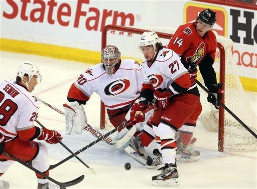Carolina Hurricanes goaltender Cam Ward (30) and Justin Faulk (27) along with Ottawa Senators' Colin Greening (14) look on as Hurricanes' Alexander Semin (28) attempts to clear the puck during second-period NHL hockey game action in Ottawa, Ontario, Thursday, Feb. 7, 2013. (AP Photo/The Canadian Press, Fred Chartrand)