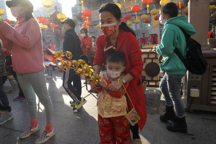Worshippers wearing face masks to protect against the spread of the coronavirus, pray at the Wong Tai Sin Temple, in Hong Kong, Friday, Feb. 12, 2021, to celebrate the Lunar New Year which marks the Year of the Ox in the Chinese zodiac. (AP Photo/Kin Cheung)