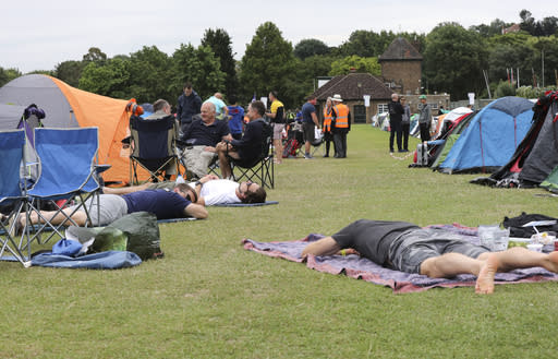 """In this Tuesday, July 9, 2019, tennis fans rest as they wait in line for tickets to enter the Wimbledon Tennis Championships in London. For many the Wimbledon experience starts in a tent as they gather in a small park across from the tournament grounds to camp out, some for days, in the hope of getting a ticket to Centre Court as they are released each day. """"The Queue"""" is a decades-old tradition that has grown to become its own phenomenon.(AP Photo/Natasha Livingstone)"""