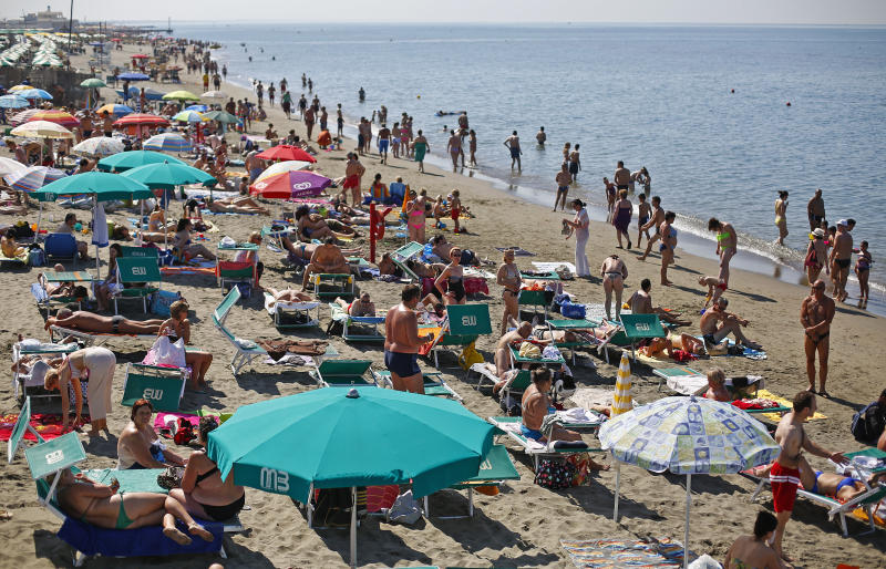 People sunbath at Ostia beach, west of Rome, June 8, 2014. Italy's beaches are a family affair - and that's a problem for the euro zone's third-largest economy. Most of the beaches along Italy's 7,500 kilometres of sun-kissed coast have for decades been managed by small businesses operating concessions that are passed on from generation to generation. Though licences are state-owned, they rarely come up for public bids, allowing Italy's balneari - or beach managers - to keep a tight grip on amenities ranging from single-shack parasol rentals to up-market bars and restaurants. To match Insight ITALY-BEACHES/ Picture taken June 8, 2014. REUTERS/Max Rossi (ITALY - Tags: TRAVEL BUSINESS ENVIRONMENT)