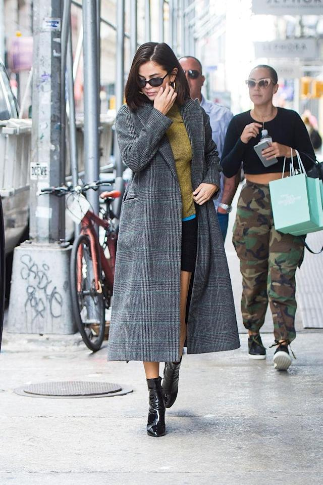 <p>For a day out in Chelsea, Gomez paired a miniskirt with an olive green sweater and a long plaid coat. A standout accessory of the week, Gomez's outerwear makes an appearance in multiple looks of hers. (Photo: Getty Images) </p>